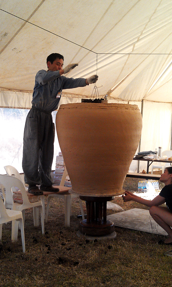 Lee Kang Hyo positioning the coal burner inside the pot